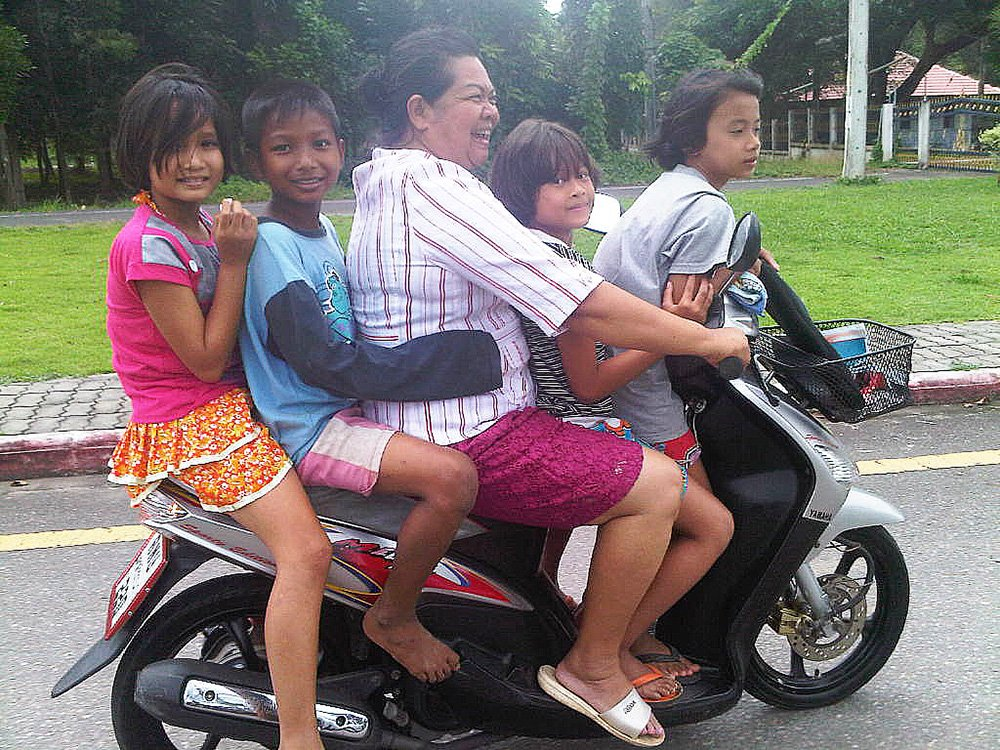 Motorbike in Thailand, smiling Thai people.